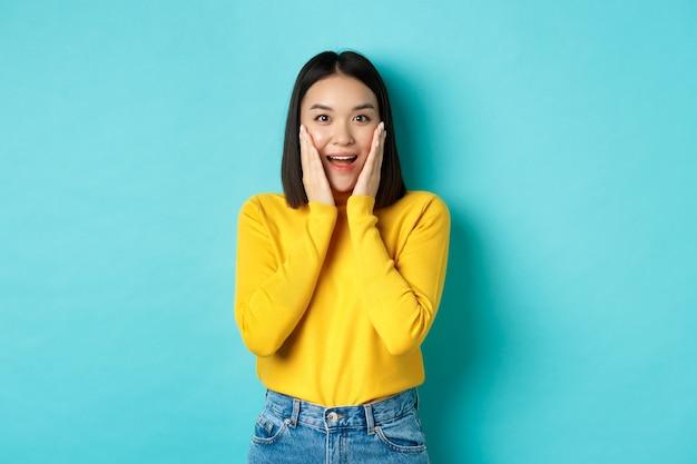 Immagine di una donna asiatica allegra e sorpresa che controlla la promozione, ansimando stupita, in piedi su sfondo blu