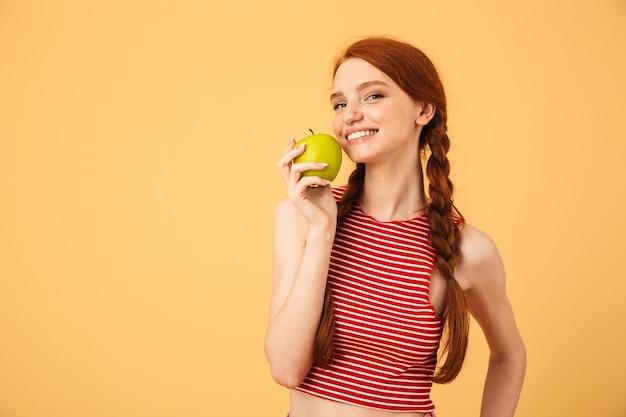 Immagine di una giovane bella donna rossa dai capelli rossi allegra che posa isolata sopra la mela gialla della tenuta della parete.