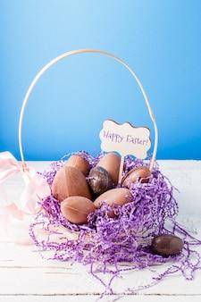 Immagine di pollo, uova di cioccolato, cestino di carta decorativa viola, auguro buona pasqua
