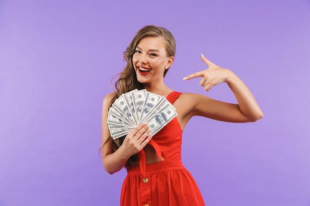 Primo piano di immagine della donna felice che porta vestito rosso che sorride e che tiene fan dei soldi del dollaro