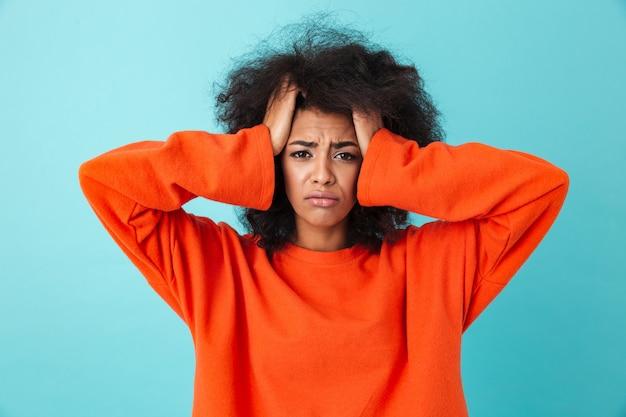 Primo piano di immagine della donna frustrata in camicia rossa che guarda e che afferra testa con capelli irsuti, isolata sopra la parete blu