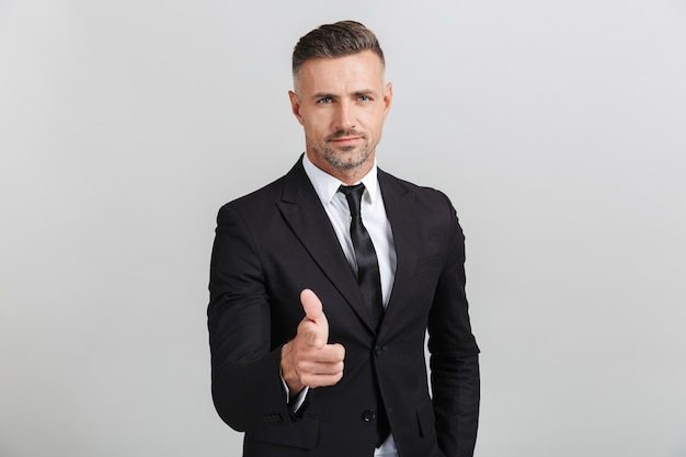 Immagine di un uomo d'affari adulto sicuro in abito formale che punta il dito contro di te isolato