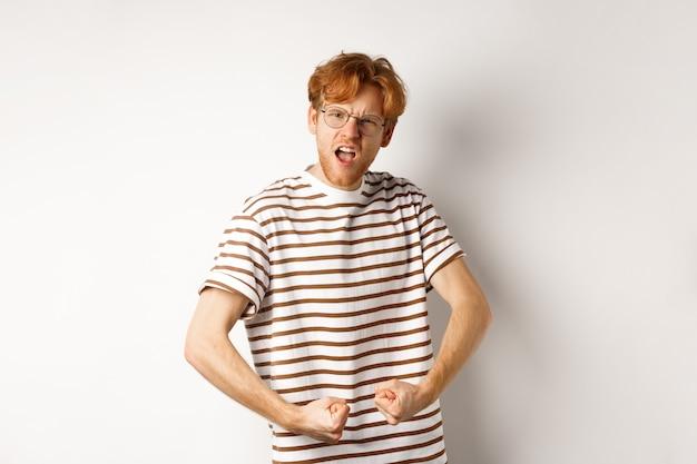 Immagine di un uomo sicuro e forte rossa che flette i bicipiti, mostrando i muscoli dopo la palestra, in piedi su sfondo bianco