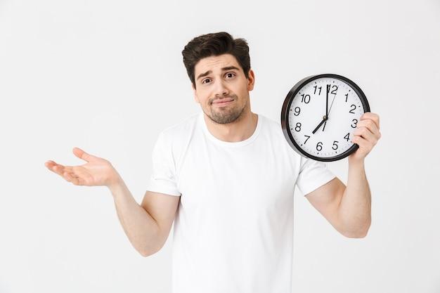 Immagine di un giovane confuso in posa isolato su un muro bianco che tiene l'orologio.