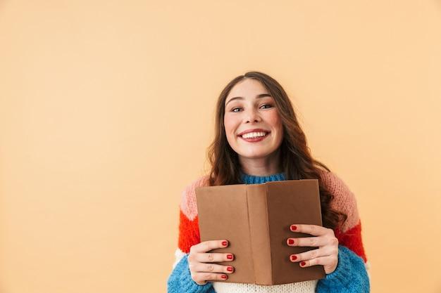 Immagine della donna 20s contenuto con i capelli lunghi che sorride e che legge il libro, stante isolato