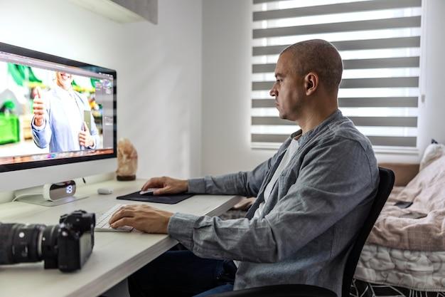 Correzione dell'immagine in un programma di elaborazione delle foto. un uomo in ufficio si siede a una scrivania accanto a una fotocamera professionale nera con un obiettivo