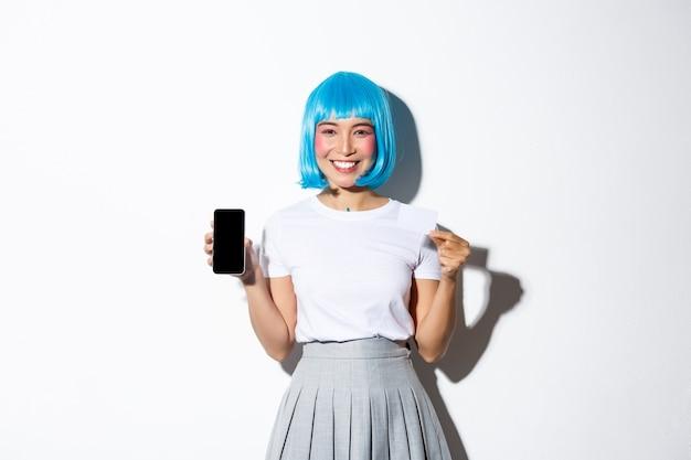 Immagine della ragazza asiatica carina vestita come personaggio anime in parrucca blu, tenendo la carta di credito e mostrando lo schermo del telefono cellulare