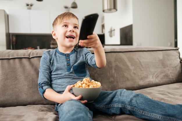 Immagine di un ragazzo carino seduto sul divano con in mano il telecomando mentre guarda la tv e tiene in mano i popcorn.
