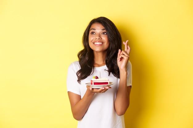 Immagine di una ragazza afroamericana carina e sognante che incrocia le dita con in mano una torta di compleanno e guarda a sinistra...