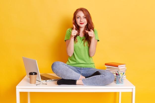 Immagine di felice giovane donna che punta il dito alla fotocamera e sorridente