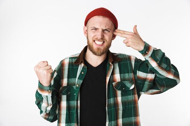 Immagine del ragazzo barbuto insoddisfatto che indossa un cappello e camicia a quadri mettendo due dita al tempio come una pistola, mentre in piedi isolato su sfondo bianco