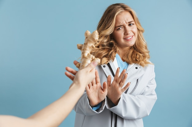 Immagine di donna 20s insoddisfatta che indossa un impermeabile che fa il gesto di arresto e guarda la radice di zenzero