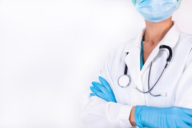 Immagine della donna medico in maschera, guanti e con lo stetoscopio