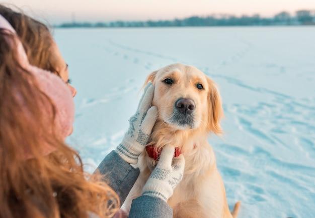 Immagine del cane golden retriever bianco in collare rosso per cani, all'aperto nel periodo invernale. animale domestico nella stagione fredda gelida