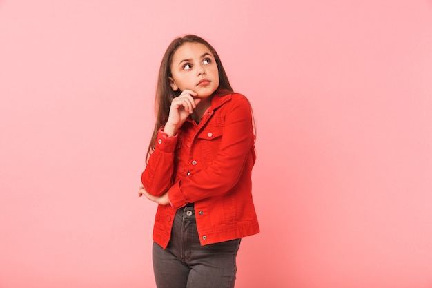 Immagine della ragazza teenager sognante nel sorridere casuale mentre levandosi in piedi, isolata sopra la parete rossa