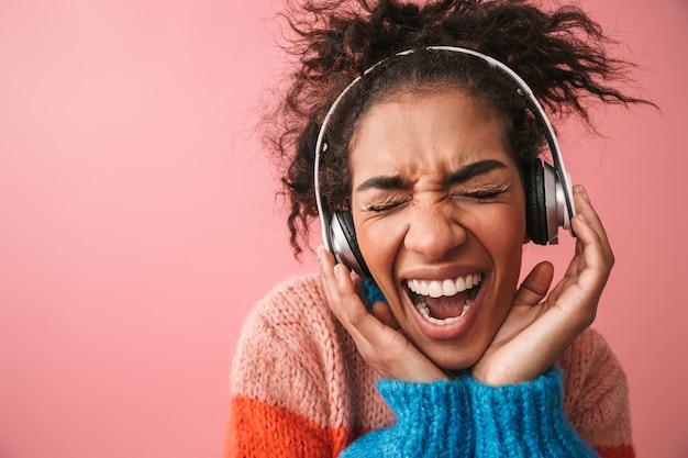 Immagine di emotiva bella giovane donna africana in posa musica d'ascolto isolata con le cuffie.