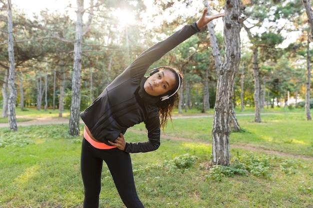 Immagine di energica donna 20s che indossa tuta nera che lavora fuori e che allunga il corpo nel parco verde