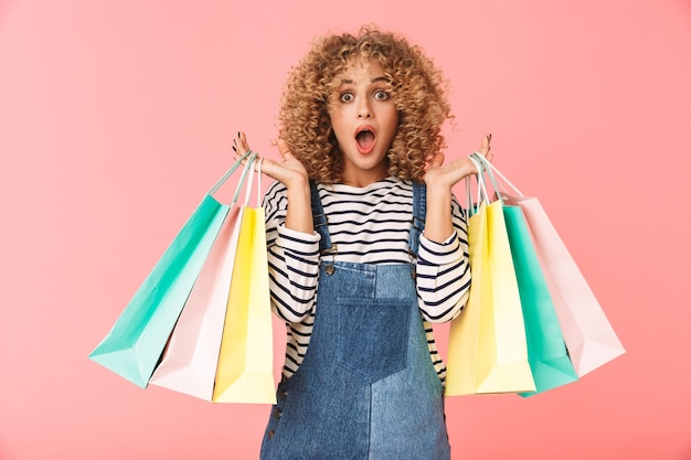 Immagine della donna riccia europea 20s che indossa abiti casual in possesso di borse della spesa colorate