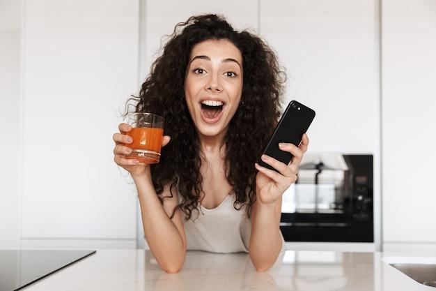 Immagine di una donna riccia europea 20s che indossa abiti di seta per il tempo libero che beve succo in cucina e guarda con la bocca aperta mentre si tiene lo smartphone nero