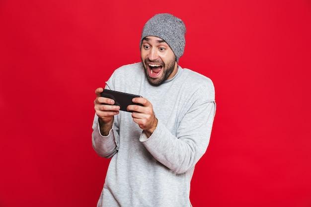 Immagine dell'uomo europeo 30s che tiene smartphone e che gioca ai videogiochi, isolata