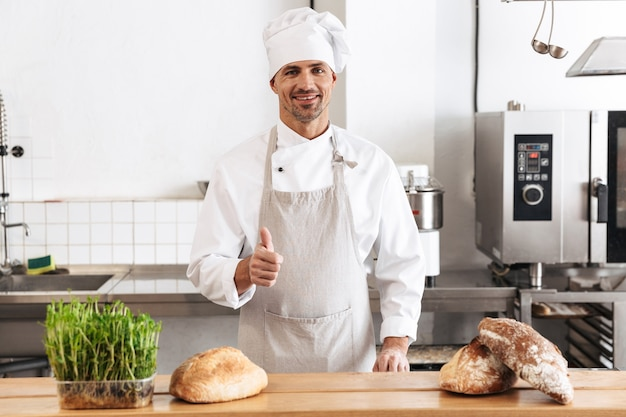 Immagine del panettiere dell'uomo europeo in uniforme bianca che sorride, mentre levandosi in piedi al forno con pane sul tavolo