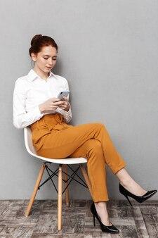 Immagine di una donna d'affari europea dai capelli rossi 20s in abbigliamento formale che utilizza il telefono cellulare mentre è seduto su una sedia in ufficio isolato su grigio
