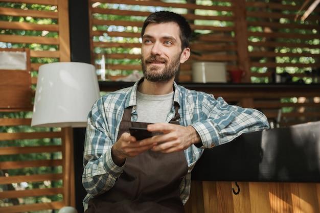 Immagine di un cameriere europeo che indossa un grembiule seduto al bar e usa il cellulare mentre lavora al bar o al caffè all'aperto