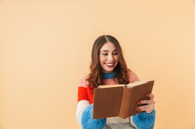 Immagine della donna europea 20s con i capelli lunghi sorridente e leggendo il libro, in piedi isolato