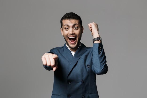 L'immagine dell'uomo d'affari felice eccitato isolato sopra la parete grigia del muro fa il gesto del vincitore che indica.
