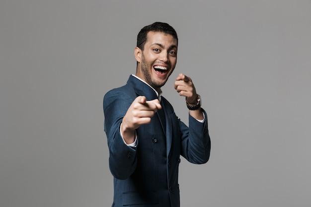 Immagine di uomo d'affari felice eccitato isolato sopra puntamento muro muro grigio.