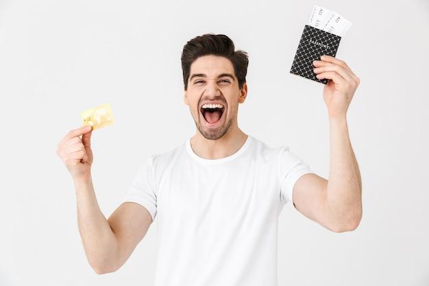 Immagine di un giovane uomo felice eccitato in posa isolato su un muro bianco in possesso di carta di credito e passaporto con biglietti.