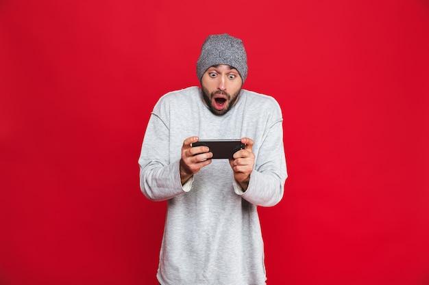 Immagine dell'uomo eccitato 30s che tiene smartphone e che gioca ai videogiochi, isolata