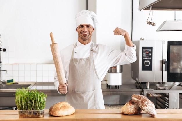 Immagine del panettiere eccitato dell'uomo in uniforme bianca che sorride, mentre levandosi in piedi al forno con pane sul tavolo
