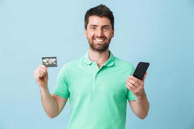 Immagine di eccitato giovane uomo barbuto bello in posa isolato su muro blu in possesso di carta di credito utilizzando il telefono cellulare.