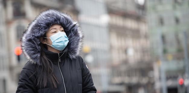 L'immagine del volto di una giovane donna asiatica che indossa una maschera per prevenire germi, fumi tossici e polvere.