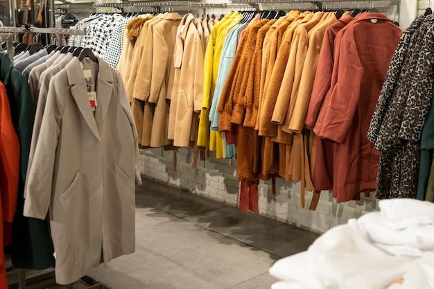 Immagine di vestiti alla moda appesi sullo scaffale in un moderno negozio di abbigliamento