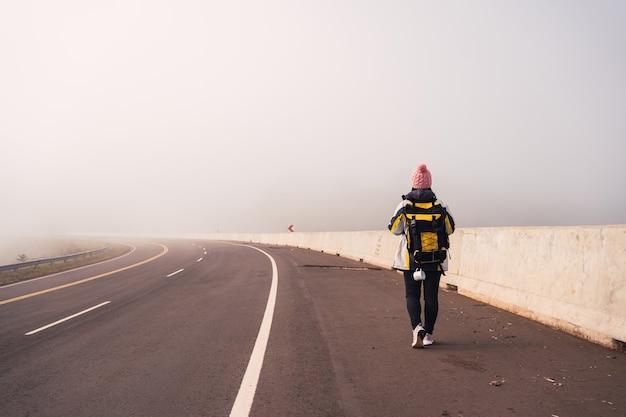 Immagine di una viandante femminile che cammina lungo una strada asfaltata.