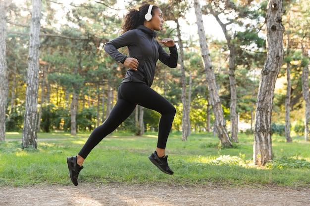 Immagine di donna 20s femminile che indossa tuta nera e cuffie che si allena, mentre correva attraverso il parco verde