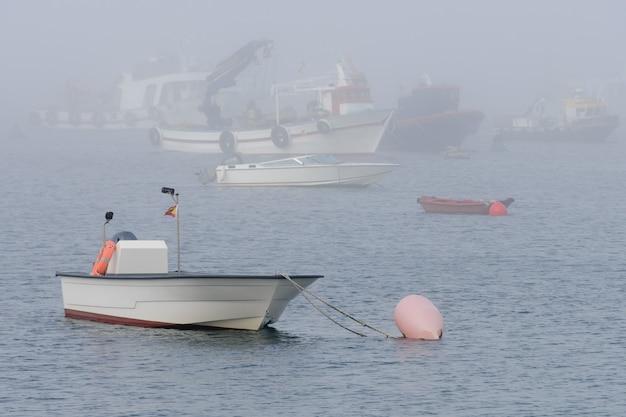 Immagine di barche da pesca ancorate in caso di nebbia
