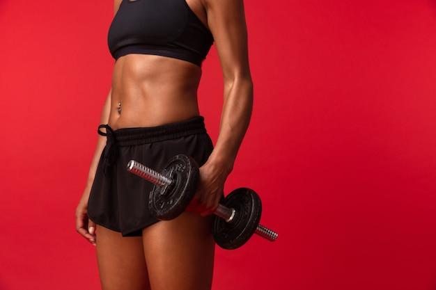 Immagine della donna afroamericana fitness in abiti sportivi neri sollevamento manubrio, isolato sopra la parete rossa