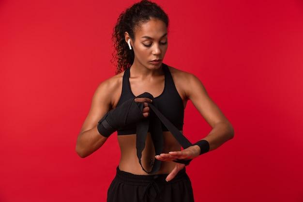 Immagine della donna afroamericana fitness in abiti sportivi neri che indossa bende sportive sulle sue mani, isolate sopra il muro rosso
