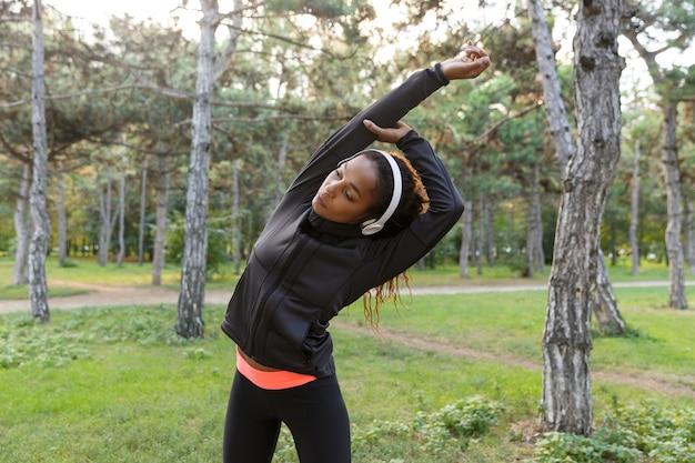 Immagine della donna di forma fisica 20s che indossa la tuta nera che lavora e che allunga il corpo nel parco verde