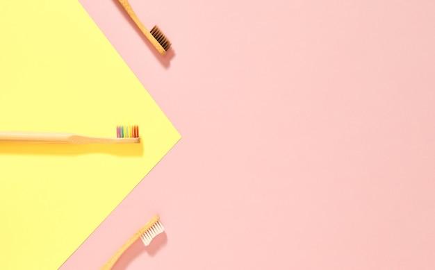 Immagine dall'alto di tre spazzolini da denti in legno con setole marroni e bianche arcobaleno disposte in diagonale e in linea su uno sfondo rosa con un triangolo giallo in isometrico