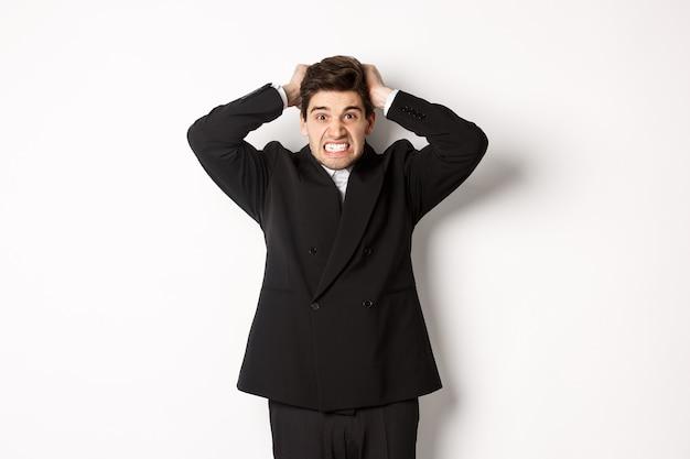 Immagine di un uomo d'affari frustrato e arrabbiato in abito nero, che si strappa i capelli sulla testa e fa una smorfia arrabbiata, in piedi teso su sfondo bianco