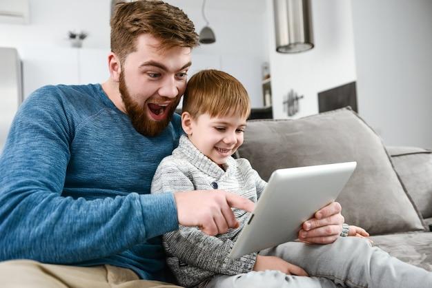 Immagine della famiglia divertente che utilizza il computer tablet all'interno.