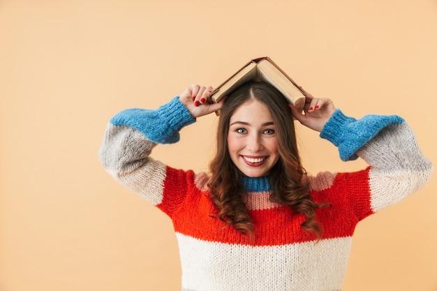 Immagine di divertente donna 20s con i capelli lunghi che ride e che tiene il libro sulla sua testa, in piedi isolato