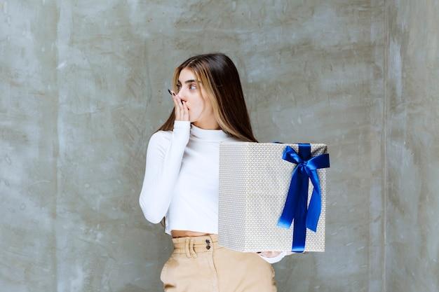 Immagine di un modello di ragazza che tiene una scatola attuale con fiocco isolato su pietra