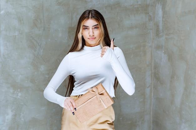 Immagine di un modello di ragazza con un presente di carta che mostra il pollice in su sulla pietra