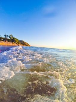 Immagine dello scatto go pro di onde bianche schiumose che si infrangono contro la spiaggia al mattino