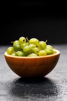 Immagine di bacche di uva spina in tazza di legno su sfondo nero